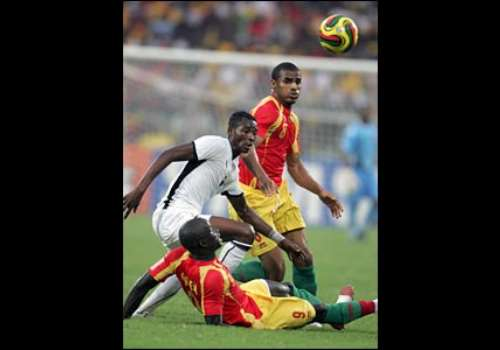 Ghana's John Pantsil fights for the ball with Kanfory Sylla and Victor Correa of Guinea