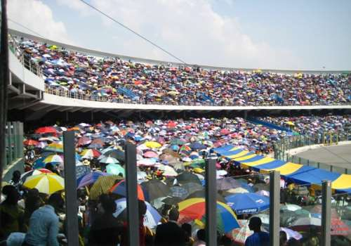 Conventioneers hold up umbrellas to protect them against heat