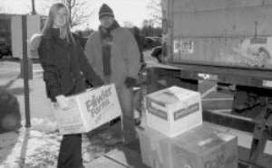 Monmouth University of Social Work student Jillian Tomiak and Luciand Feirrera, from Star Transport, load boxes of books into a truck.