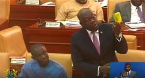 Kojo Oppongg Nkrumah displaying the fruit juice on the floor of Parliament today