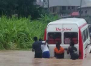 A trapped bus being pushed through the floods