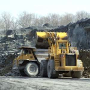 Biting deep into the earth, earth moving equipment at the site of a mining firm