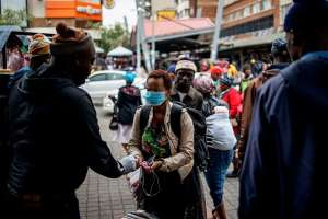 A taxi rank marshal sprays hand sanitiser on a commuter wearing a mask as a preventive measure as she arrives at the Wanderers taxi rank in Johannesburg. - Source: Marco Longari/AFP via Getty Images