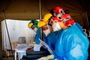 Health workers fill out documents before performing tests for COVID-19 at the screening and testing tents set up at the Charlotte Maxeke Hospital in Johannesburg. - Source: Photo by Michele Spatari / AFP via Getty Images