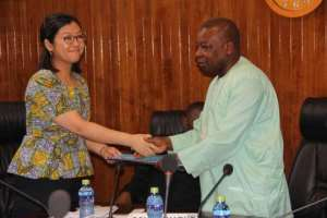 Agyeman Many (right) in a symbolic exchange of the document with Ms Maki after the signing