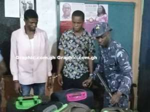 The suspects with a Customs officer after they had been arrested