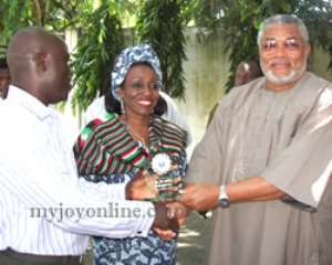 Anthony Corsy, Lecturer in Mass Communication at the Kaduna State University presents the plaque to Mr & Mrs Rawlings
