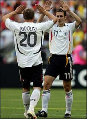 Podolski celebrates his second goal with Miroslav Klose, who played a big part in both of his strike partner's goals