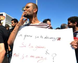 A protester in Tunis openly smokes a cigarette and holds a placard reading in French