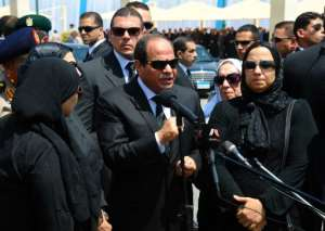 A handout picture released by the Egyptian Presidency on June 30, 2015, shows Egyptian President Abdel Fattah al-Sisi (C) talking to media as he stands with the family of the late Egyptian state prosecutor Hisham Barakat.  By HO (Egyptian Presidency/AFP)