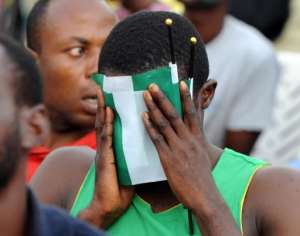 A Nigeria fan covers his face with the country's green and white flag as he watches the 2014 FIFA World Cup round of 16 football match between France and Nigeria at a viewing centre in Lagos on June 30, 2014.  By Pius Utomi Ekpei (AFP/File)