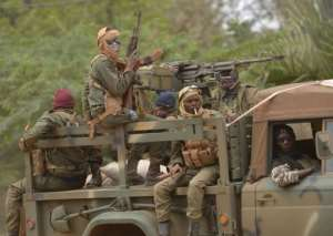 Malian soldiers patrol aboard a vehicule mounted with a machine gun in a street of Diabaly on January 26, 2013.  By Eric Feferberg (AFP)