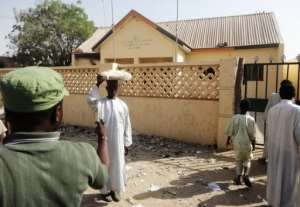 A street vendor passes by a partially burnt police station in the northern Nigerian city of Kano on January 25, 2012.  By Aminu Abubakar (AFP/File)