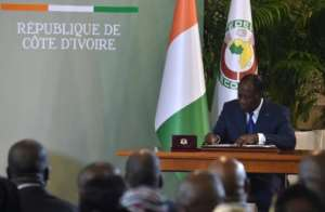 Ivory Coast's president Alassane Ouattara signs the country's revisited constitution on November 8, 2016 at the presidential palace in Abidjan.  By Issouf Sanogo (AFP)