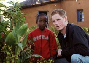 Britain's Prince Harry, seen here with a young boy, in Lesotho, on April 24, 2006.  By John Stillwell (Pool/AFP/File)