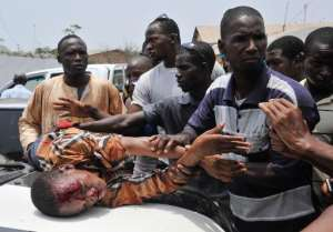 People assist a protester injured during clashes with police at an anti-government protest in Conakry on April 20, 2015.  By Cellou Binani (AFP/File)