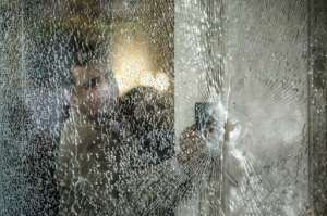 An Egyptian forensic expert inspects a bullet riddle window at the entrance of the Three Pyramids hotel in Cairo's al-Harm district on January 7, 2016.  By Khaled Desouki (AFP)