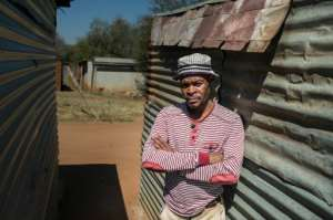 Mohlaudi Mohlaudi stands outside his house in Marikana, where in 2012 police opened fire on striking platinum workers, killing 34 miners and wounding dozens more.  By Mujahid Safodien (AFP)