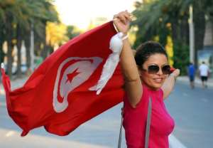 A Tunisian woman holds her national flag in Tunis,.  By Fethi Belaid (AFP/File)