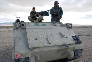 Tunisian soldiers stand on their tank in Dernaya Mountains in the Kasserine region, near the Algerian border, on December 11, 2012.  By Abderrazek Khlifi (AFP/File)