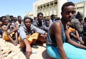 Migrants from sub-Saharan Africa sit at a center for illegal migrants in the al-Karem district of the Libyan eastern port city of Misrata on April 15, 2015.  By Mahmud Turkia (AFP)