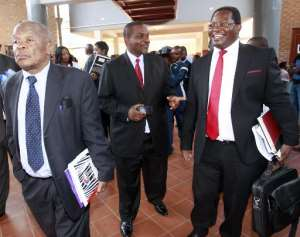 Zambia's Director of Public Prosecutions Mutembo Nchito (C) chats with former president Rupiah Banda's lawyers Erick Silwamba (R) and Patrick Mvunga (L) as they leave the Lusaka magistrates' court on March 26, 2013.  By Joseph Mwenda (AFP/File)
