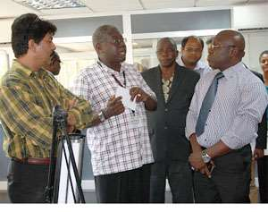 Reuben Damptey (2nd left), explaining a point to Inusah Fuseini (in tie) during a tour of some facilities at PMMC.
