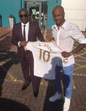 Ghana winger Dede Ayew with father Abedi Pele minutes after signing the deal