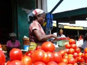 A Woman manages her product at a market in Accra, Ghana