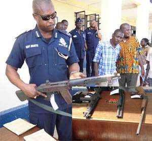 DCOP Kofi Baokye examing one of the robbers' weapons. INSET: The weapons and ammunitions