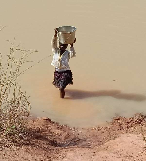 A young girl fetching water from the Dam in the Taha Community
