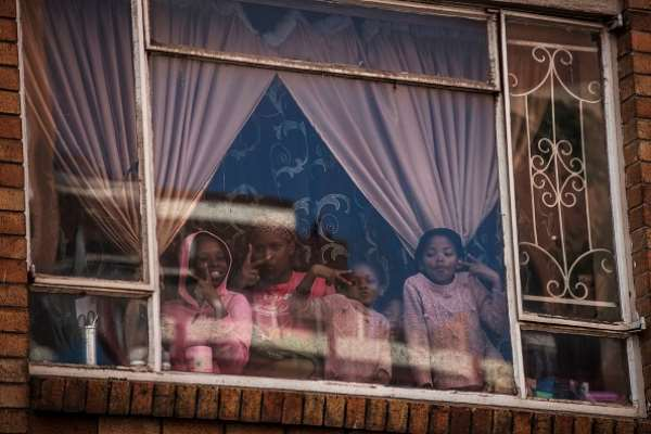 Children at window of a building in Hillbrow, Johannesburg. Children will be vulnerable if vaccinations are postponed. - Source: Photo by Marco Longari/AFP via Getty Images