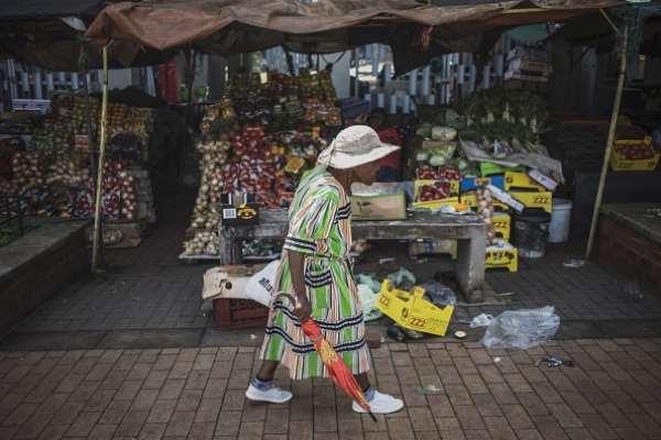 A woman walks past a market stall in Kliptown, Soweto. - Source: