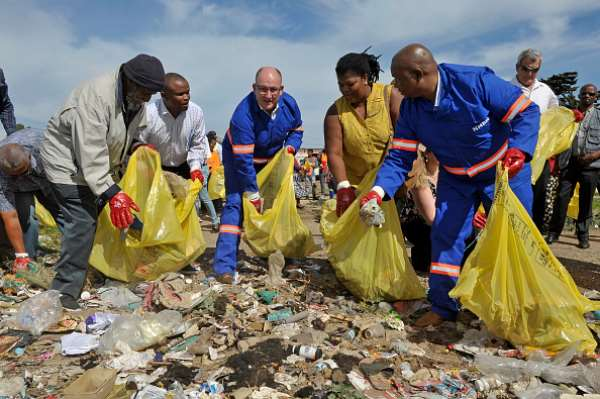 Former Nelson Mandela Bay Mayor Athol Trollip, from the DA, third from left, and his deputy Mongameli Bobani, from the UDM, extreme right, help clean up a street in 2017.   - Source: by Werner Hills/Foto24/Gallo Images/Getty Images