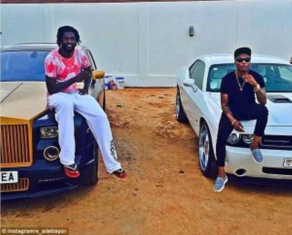 Emmanuel Adebayor (left) poses with his expensive car with Nigerian recording artist Wizkid (right)