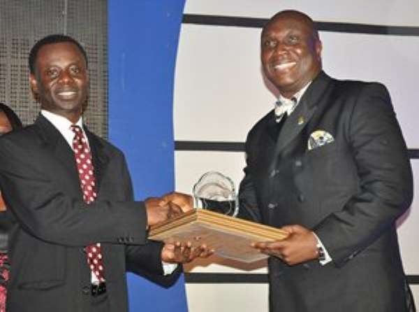 Samuel Sarpong GÇô Chief Transformation Officer of GCB receiving the award from Mr. Clifford Duke Mettle, President of the Chartered The Chartered Institute of Bankers