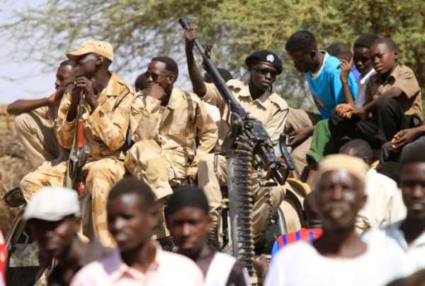 Sudanese soldiers keep watch as they sit next to civilians in the Shangil Tobaya area for displaced people in North Darfur state, on June 18, 2013.  By Ashraf Shazly (AFP/File)