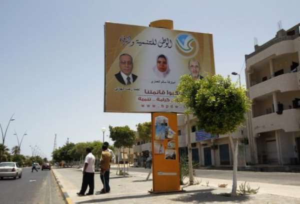 Libyan men stand near an election campaign poster in Sirte.  By Mohammed Abed (AFP)