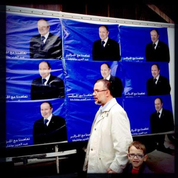 A man walks past posters of Algerian president Abdelaziz Bouteflika in Algiers on April 15, 2014.  By Patrick Baz (AFP)