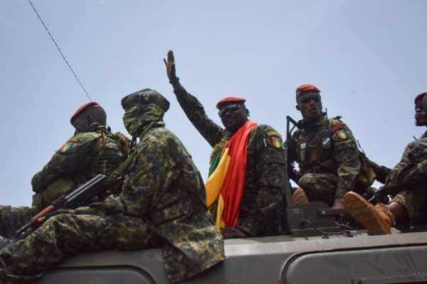 Coup leader Lieutenant Colonel Mamady Doumbouya, centre, waving to the crowd as he arrived at parliament on Monday for a meeting with outgoing ministers.  By CELLOU BINANI (AFP)