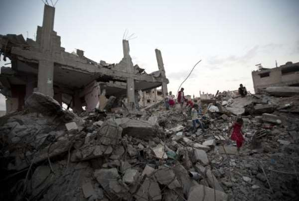 Palestinian children walk amidst the rubble of a building destroyed during the 50-day conflict between Hamas militants and Israel, in the Shejaiya neighbourhood in the east of Gaza City, October 12, 2014.  By Mahmud Hams (AFP)