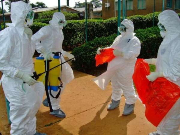 Officials from the World Health Organization wear protective gear as they prepare to enter Kagadi Hospital.  By Isaac Kasamani (AFP/File)
