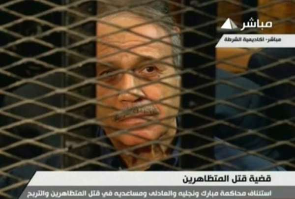 An image taken from Egyptian state TV shows former Egyptian interior minister Habib al-Adly sitting behind bars during a hearing in his retrial at the Police Academy in Cairo on July 6, 2013.  By  (Egyptian TV/AFP)