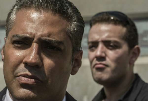 Al-Jazeera journalists, Canadian Mohamed Fahmy (left) and Egyptian Baher Mohamed, wait outside Cairo's Torah prison where their trial was due to take place on July 30, 2015.  By Khaled Desouki (AFP/File)