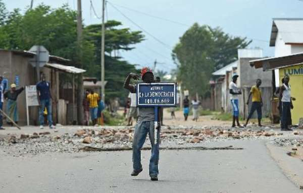 A protestor opposed to Burundian President Pierre Nkurunziza's third term holds a road sign reading