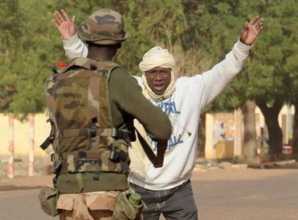 A Malian soldier arrests a man at a checkpoint on February 11, 2013, in Gao.  By Pascal Guyot (AFP)