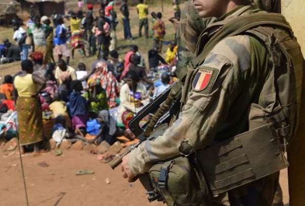 A French soldier taking part in 'Operation Sangaris' standing guard as Muslim people wait to seek refuge at the Boali church, some 100km north of Bangui.  By Eric Feferberg (AFP/File)