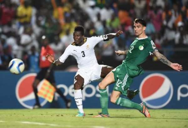 Ghana forward Asamoah Gyan (L) scores a goal past Algeria defender Carl Medjani during the 2015 Africa Cup of Nations group C match in Mongomo, Equatorial Guinea on January 23, 2015.  By Carl De Souza (AFP)