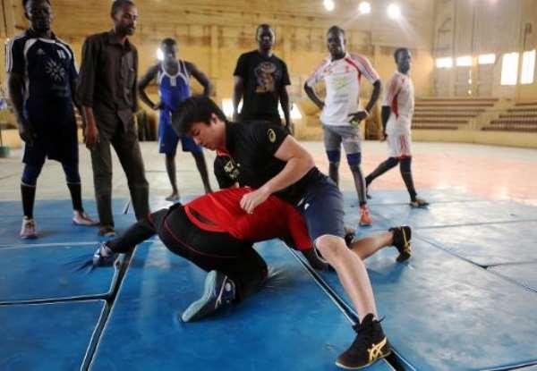 Japanese coach Kosuke Sunagawa (R) demonstrates a wrestling hold during his last training session in Khartoum.  By Ashraf Shazly (AFP/File)