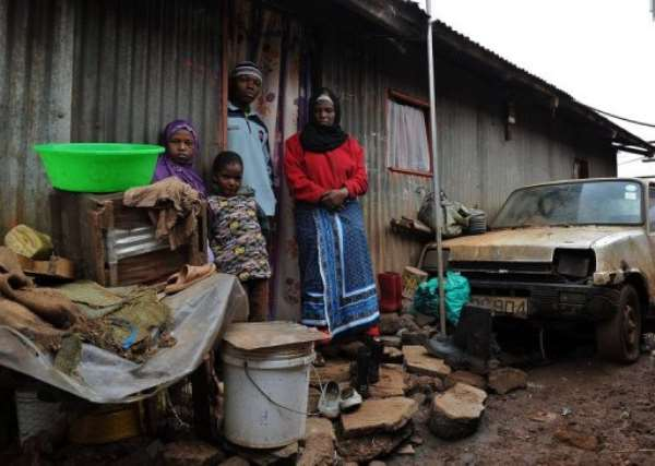 Latifah Naiman (R) stands with her children in front of her house in the Nairobi slum of Kangemi on August 3, 2013.  By Tony Karumba (AFP)